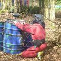 Paintballer hiding behind drum